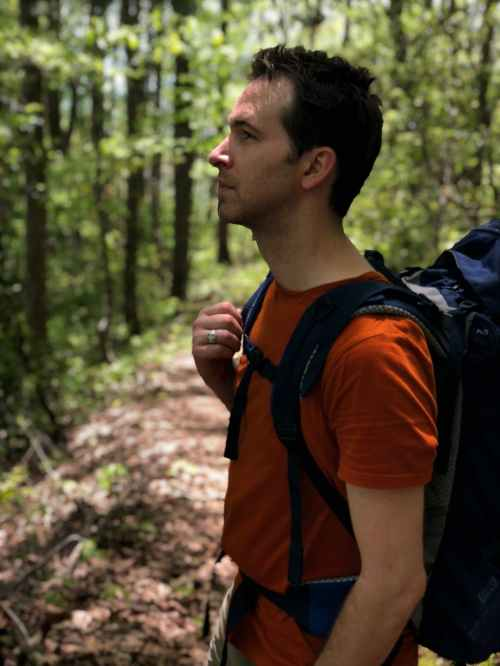 man in red crew neck shirt carrying blue hiking backpack